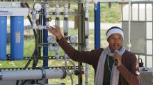 Diné College student and Indige-FEWSS participant Larry Moore demonstrates the solar-powered water filtration system to community members on Navajo Nation.