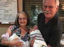 An older couple hold two newborn babies in a hospital room.