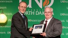 A man accepts a framed certificate from another man in front of a green University of North Dakota backdrop