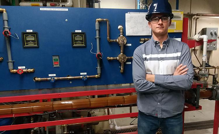 A man with his arms crossed, wearing a hard-hat and standing before machinery.