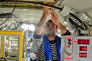 Doctoral student Hossein Dadashazar collects cloud water samples aboard the Navy Twin Otter