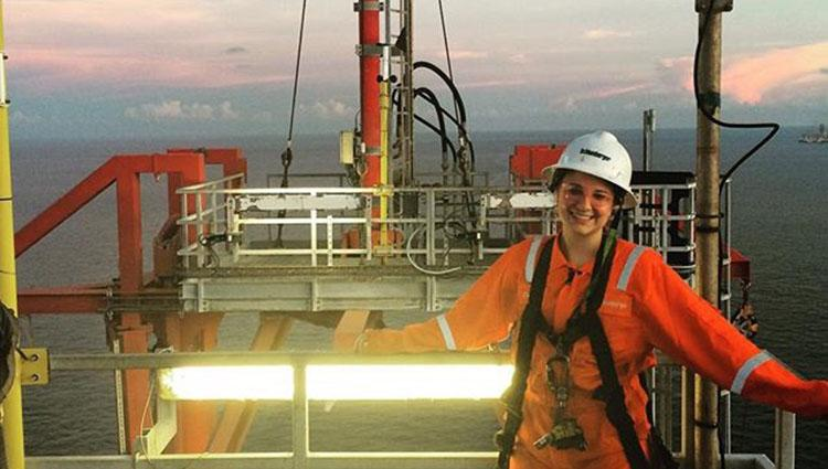 A woman in a bright orange jumpsuit and hard hat stands on the deck of a ship at sea