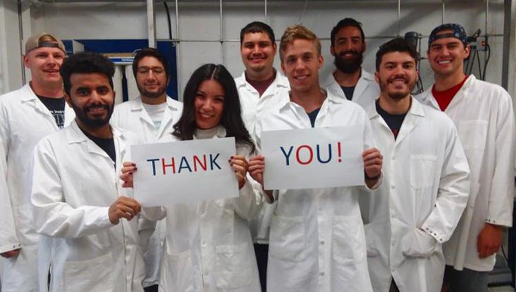 "A group of men and women in lab coats standing in a group, two people in front holding a sign that reads ""thank you"""