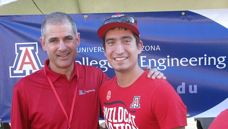 Two men in red University of Arizona shirts smile in front of a blue College of Engineering banner