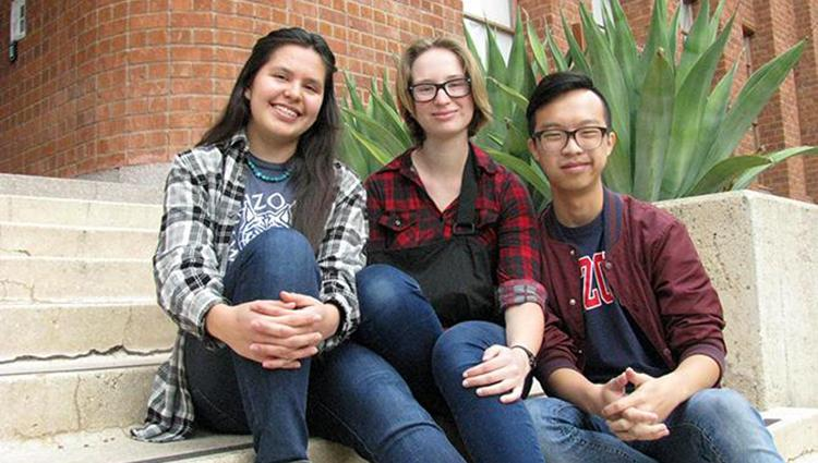 Two female students and one male student sitting together on the front steps of a building.