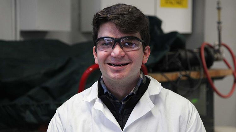 Gabriel Schirn smiling, wearing protective eyewear and a lab coat in a chemical engineering lab