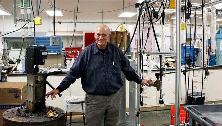 Don Gervasio, wearing a long-sleeved blue shirt, stands between a pump and pipe in a laboratory with tubes hanging in the background.
