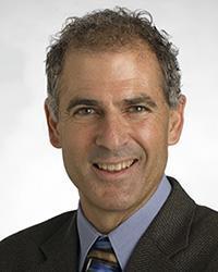 Headshot of Anthony Muscat wearing a gray jacket and blue shirt