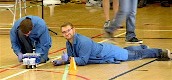 Two chemical engineering students construct a Chem-E-Car in a gymnasium