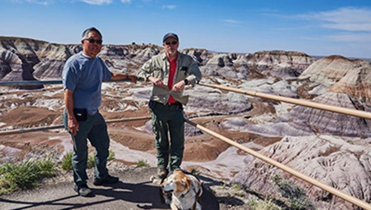 Two men in hiking clothes stand in front of a brown-and-gray desert vista with a brown-and-white dog at their feet