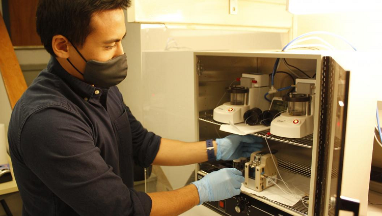 Suchol Savagatrup, wearing gloves and a mask, reaching into a cabinet in his laboratory.