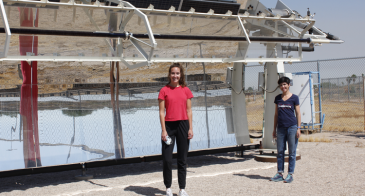 Mikah Inkawhich and Kerri Hickenbottom standing in front of a solar-powered desalination system, which looks like a giant mirror.