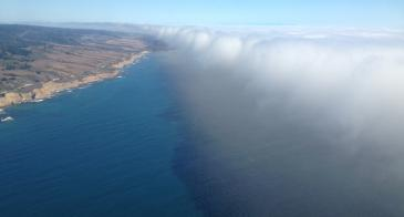 Photo from aircraft of a mass of fluffy white clouds over the ocean approaching a coastline.